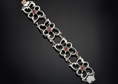Silver linked bangle decorated with 18ct yellow gold mounts set with Rhodolite garnets.