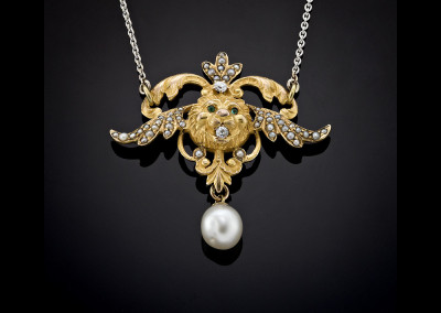 Winged lions head pendant set with emeralds and diamonds decorated with pearls and hanging pearl drop